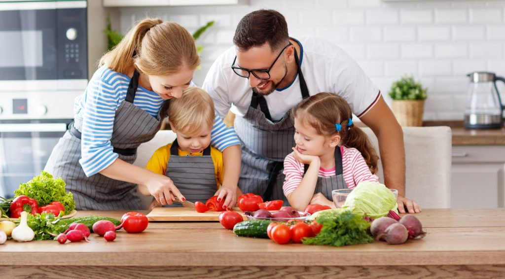 happy family with children preparing vegetable salad at home